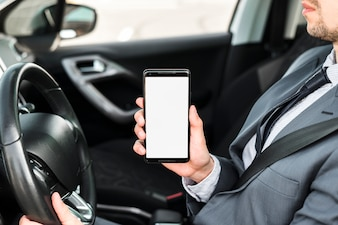 Close-up of a businessman driving car showing mobile phone with white display screen