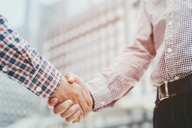2人の同僚間のビジネスマンの握手のクローズアップ。または交渉された合意の成功した仕事。