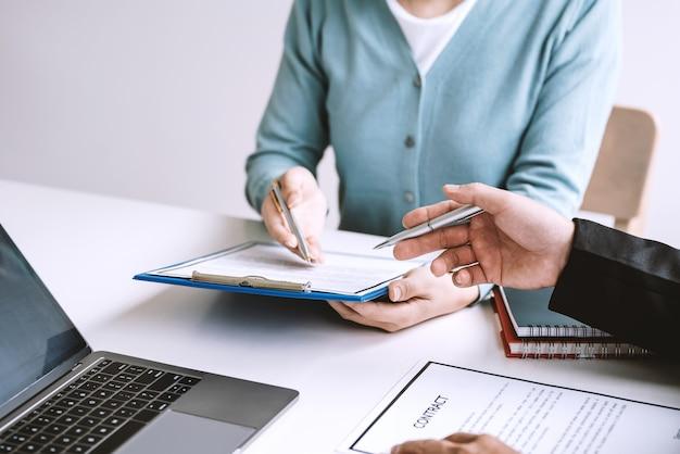 ペンを持っているビジネスマンのクローズアップは、オフィスで契約書に署名する条件を読んだ。