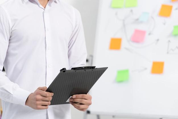 フリップチャートの近くに立って手で黒いクリップボードを保持している実業家のクローズアップ