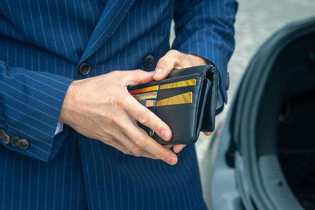 정장을 입은 사업가가 비즈니스 가죽 지갑을 엽니다.