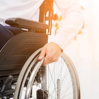 車椅子のホイールに実業家の手のクローズアップ