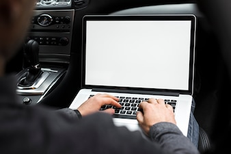 Close-up of a businessman's hand using laptop sitting in the car