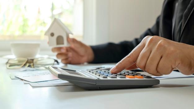 Крупный план бизнесмена, использующего калькулятор и проверяющего бухгалтерские отчеты, концепция инвестиций в финансирование работы