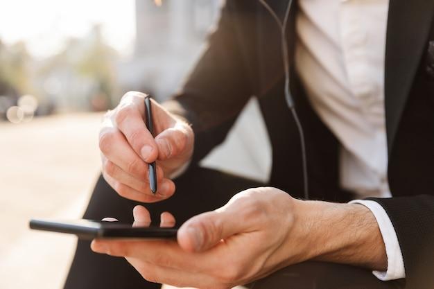 Крупным планом бизнесмена с помощью мобильного телефона и стилуса на открытом воздухе
