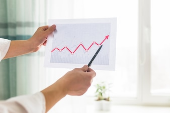 Close-up of a businessperson's hand analyzing graph at workplace