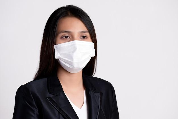 Крупным планом бизнес-леди в костюме носить защитную маску