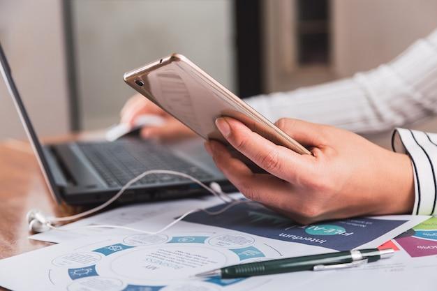 Крупный план рук бизнес-леди с помощью мобильного телефона и портативного компьютера.