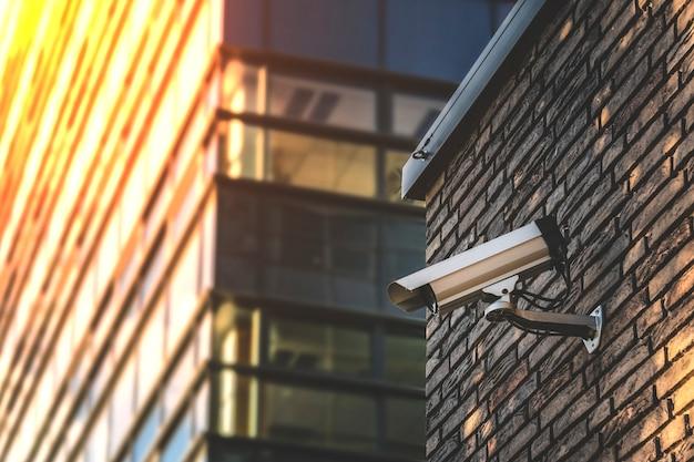 Крупным планом фотоаппарат, прикрепленный к кирпичной стене снаружи. камера слежения на современном здании. видеооборудование для контроля систем безопасности на открытом воздухе.