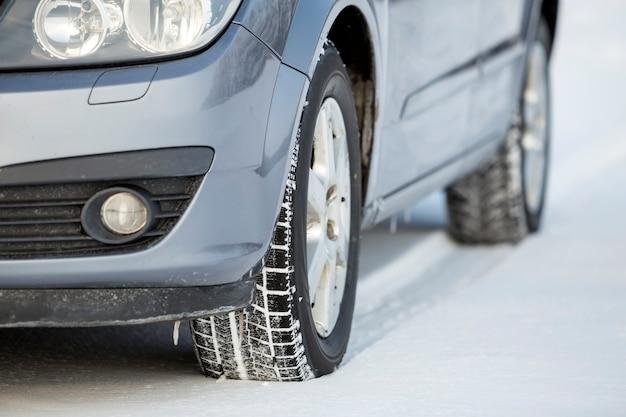 Закройте автомобильную шину, припаркованную на заснеженной дороге в зимний день. концепция транспорта и безопасности.