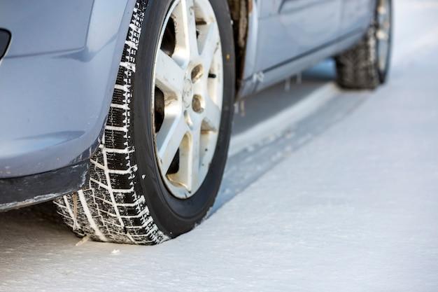 Закройте вверх автошины автомобиля припаркованной на снежной дороге на зимний день. концепция транспорта и безопасности.
