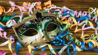 Close-up of a carnival mask with colorful streamers on wooden desk
