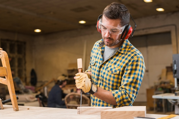 Конец-вверх плотника ударяя молоток на зубиле в деревянном блоке в мастерской