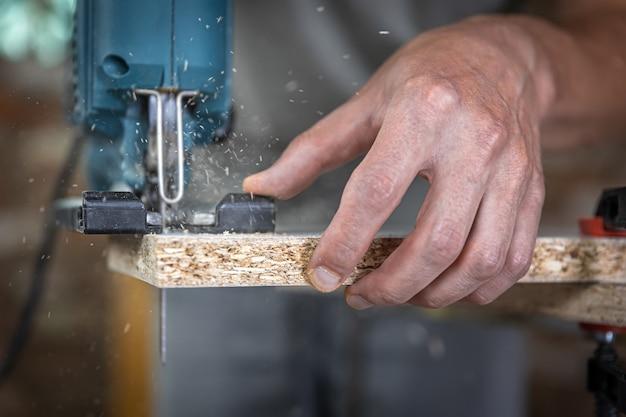 ジグソーで木を切る過程での大工の手のクローズアップ。