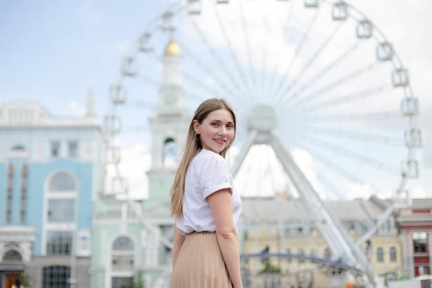 Крупный план кавказской блондинки в белой футболке смотрит через плечо на фоне колеса обозрения на улице