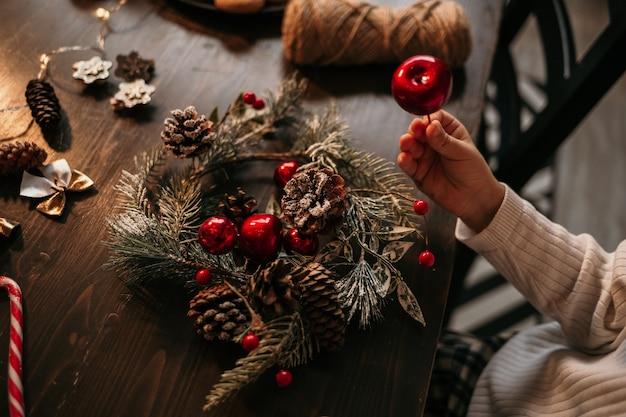 テーブルに座ってクリスマスツリーの花輪を作る白人の子供のクローズアップ