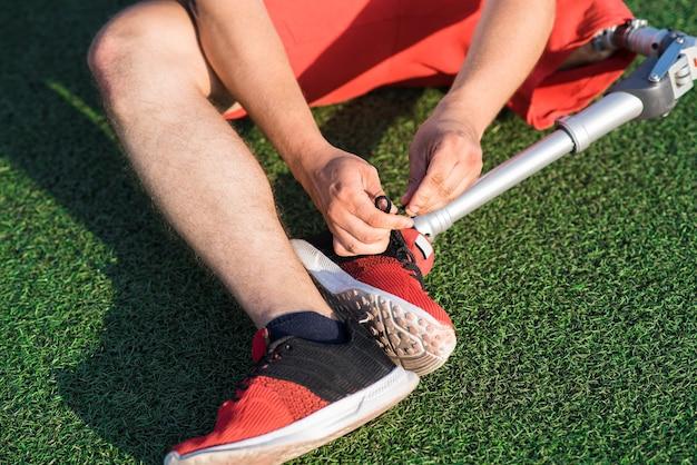 スタジアムのフィールドに座ってスニーカーでレースを結ぶ義足を持つ白人男性のクローズアップ。