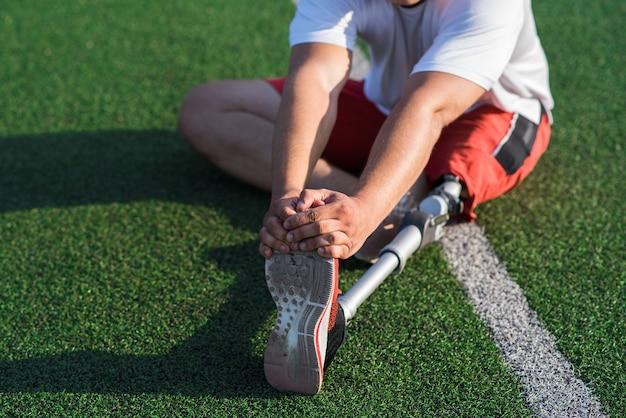 スタジアムのフィールドに座っている間、義足を伸ばしている白人男性のクローズアップ。スポーツのコンセプト。