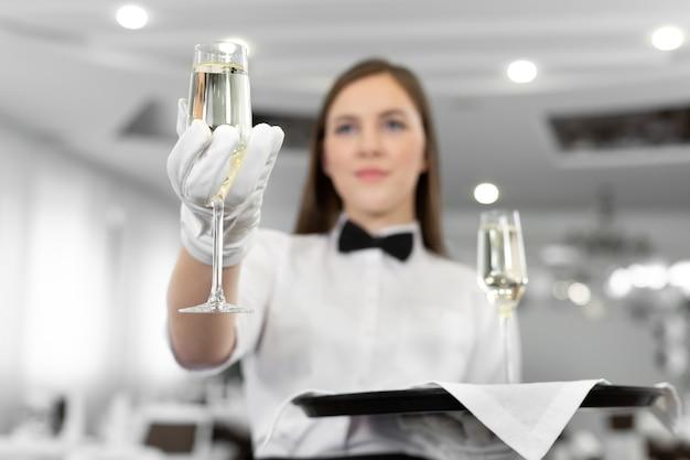 Крупным планом бокал шампанского в руках официант-сомелье