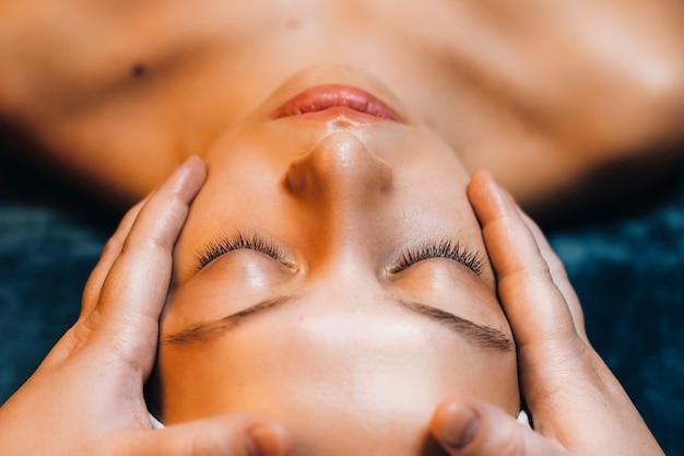 웰빙 스파 리조트에서 페이셜 마스크를 사용하는 동안 닫힌 눈으로 leanin 매력적인 여자 얼굴 닫습니다.