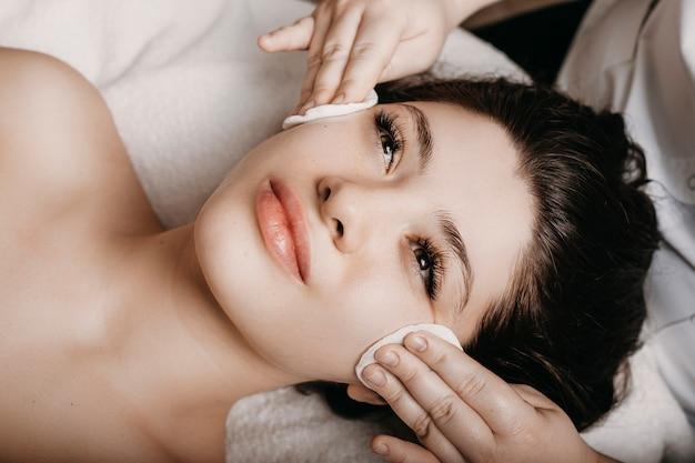 웰빙 리조트에서 히알루 론산으로 마스크하기 전에 피부 관리 루틴을 갖는 눈으로 스파 침대에 기대어 매력적인 여자의 닫습니다.