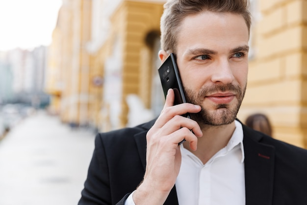 Крупным планом очаровательный молодой бизнесмен в костюме, стоящий в городе, с помощью мобильного телефона