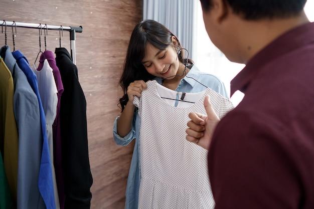 선택 하 고 옷을 구입하는 쾌활 한 부부의 닫습니다. 옷가게에서
