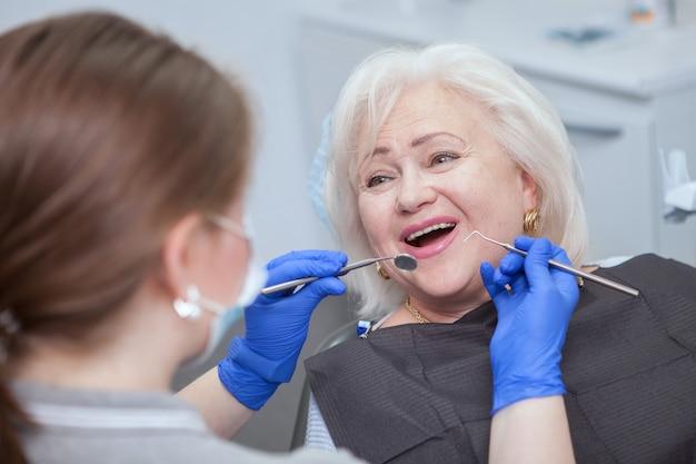 Крупным планом веселая пожилая женщина, проходящая стоматологическое обследование у своего стоматолога