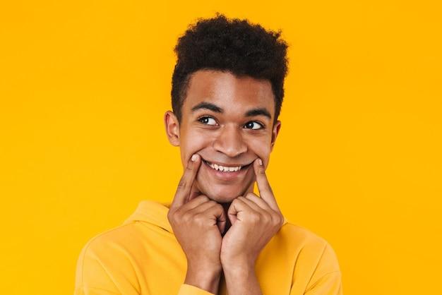 黄色の壁の上に孤立して立って、目をそらしている陽気な若いティーンエイジャーの少年のクローズアップ