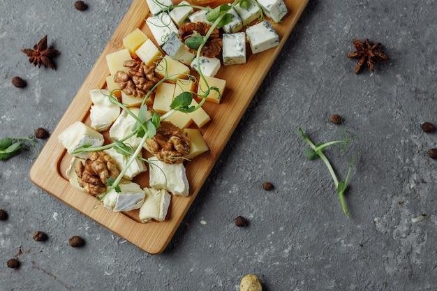 チーズプレートのクローズアップ。 4種類のチーズ、ソフトホワイトブリーチーズ、カマンベール、セミソフトブリーチーズ、ブルー、ロックフォール、ハードチーズ。クルミ、緑のブドウ。美しいサーブ。レストラン。