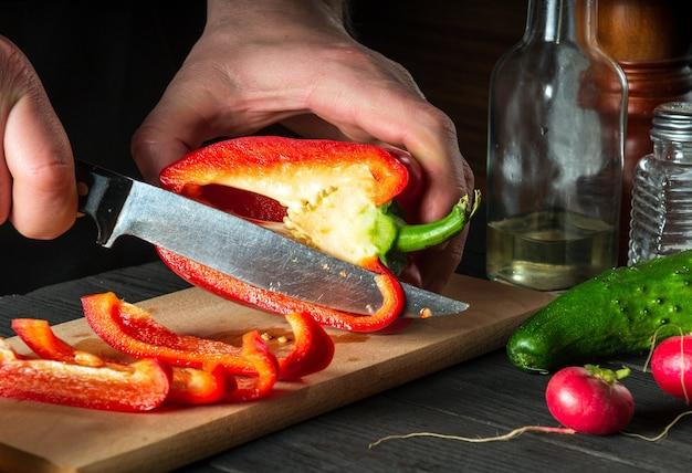 Крупным планом руки шеф-повара, режущие перец на разделочной доске