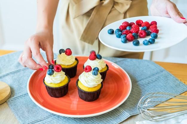 着色された果実、ラズベリー、ブルーベリーのカップケーキを飾るシェフの手のクローズアップ。