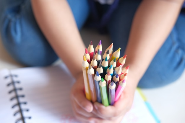 多くのカラフルな鉛筆を持っている子供の手のクローズアップ