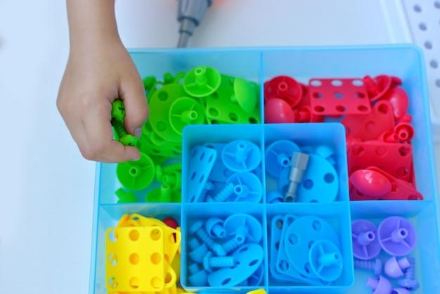 ドライバー、ドライバー、マルチカラーの幾何学的なフィグを備えたシュルカで子供の教育コンストラクターパズルをプレイしている子供のクローズアップ。創造的な未就学児の開発コンセプト。