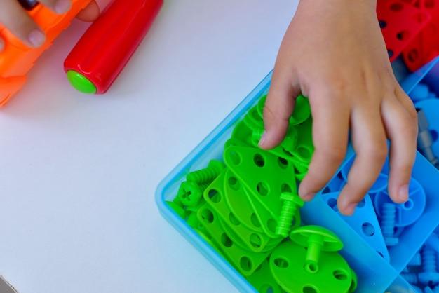 스크루드라이버, 스크루드라이버, 다양한 색상의 기하학적 퓨그가 있는 슈루카를 사용하여 어린이 교육 구성자 퍼즐을 재생하는 어린이의 클로즈업. 창의적인 미취학 아동 개발 개념입니다.