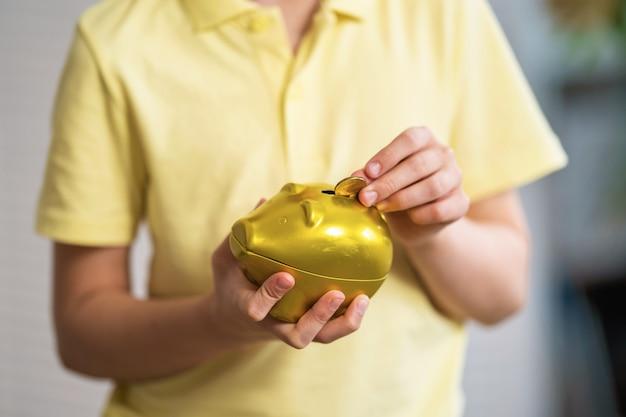 Крупным планом ребенка положить монеты в копилку.
