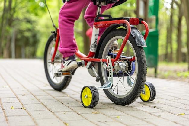 Крупным планом - ребенок едет на трехколесном велосипеде.