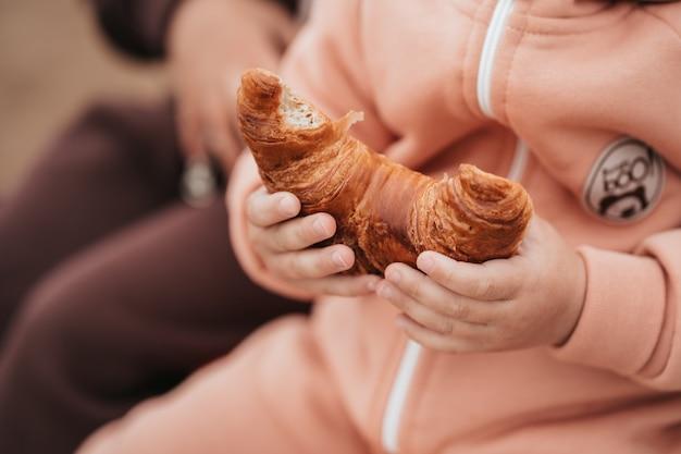 Крупным планом - детская рука и круассан. ребенок ест булочку. аппетитный круассан в руках ребенка.