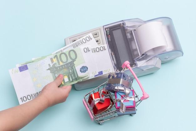 Крупным планом - рука ребенка, держащая копию банкноты 100 евро над кассовым аппаратом для покупки коробок с подарками в тележке