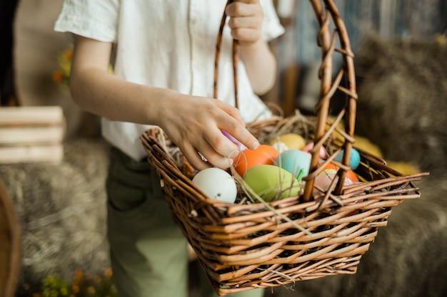 籐のかごの中のカラフルな卵を拾う子供の手のクローズアップ。イースターホリデー