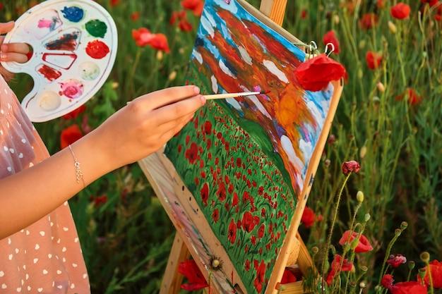 Крупный план детской руки с кистью и палитрой красок в области красных маков и картины на холсте