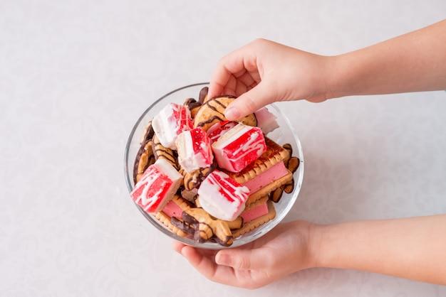 Крупным планом руки ребенка, принимая сладости. печенье и мармелад в миску на белом фоне
