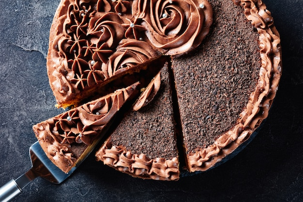 Крупный план праздничного торта с шоколадным безе, увенчанного шоколадно-сливочными розами и серебряным съедобным драже, нарезанным ломтиками на тарелке на бетонном столе, горизонтальный вид сверху