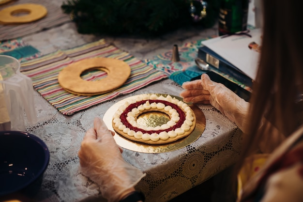 パティシエの手にあるクリスマスのジンジャーブレッドのクローズアップ、彼の肩越しの眺め。労働環境、新年の気分、新年の準備。休日を待っています。