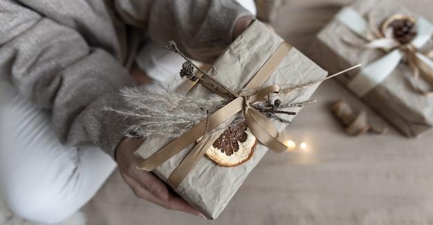 Крупным планом - рождественский подарок, украшенный засушенными цветами и сухим апельсином, завернутый в крафт-бумагу.