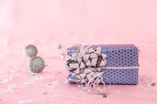 흐릿한 분홍색 배경에 크리스마스 장난감이 있는 크리스마스 선물을 클로즈업하고 공간을 복사합니다.
