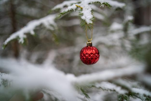 冬の森の雪に覆われた活気のある木の上のクリスマスのおもちゃのクローズアップ。
