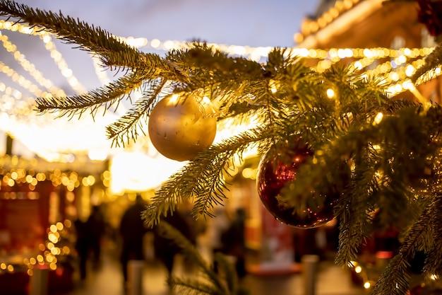 Крупным планом ветка елки с декоративными шарами, игрушками и сияющей гирляндой. мягкий фокус, размытый фон.