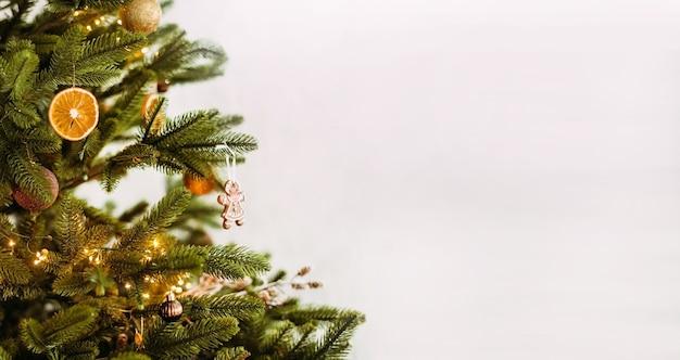 装飾おもちゃ、白い背景の上の乾燥したオレンジとクリスマスツリーのクローズアップ。