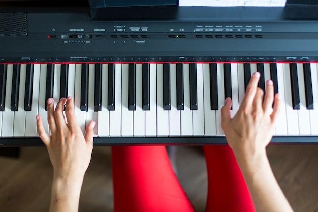 Крупный план руки девушки классического музыкального исполнителя, играющей на пианино или электронном синтезаторе (фортепианная клавиатура).